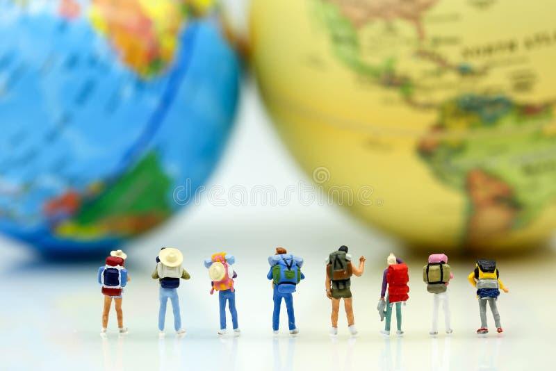 Personnes miniatures : Voyageurs avec le globe du monde et l'avion, tra photo libre de droits