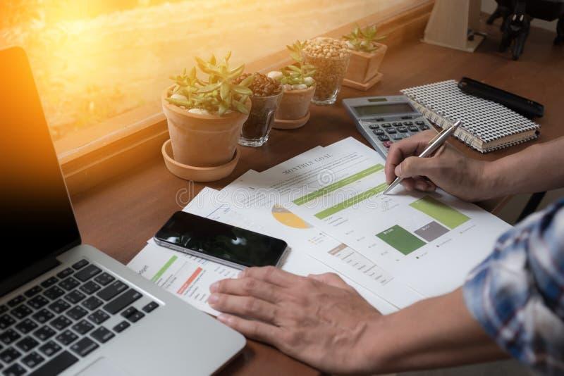 Personnes modernes faisant des affaires, des graphiques et des diagrammes étant démontrés sur le bureau en bois dans le bureau photographie stock libre de droits