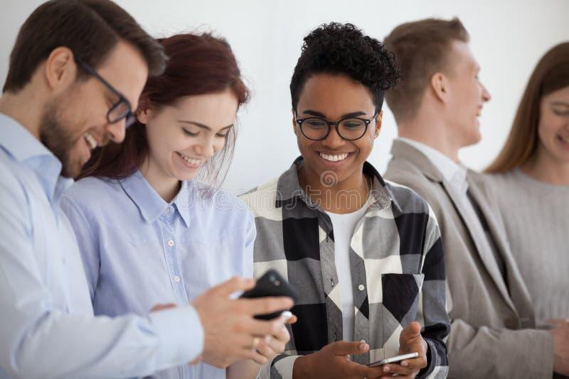 Personnes multi-ethniques de sourire tenant des téléphones ayant l'amusement avec des périphériques mobiles photographie stock
