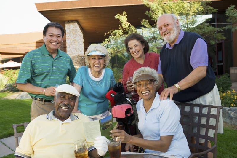 Personnes multi-ethniques heureuses à la station de vacances de golf photographie stock