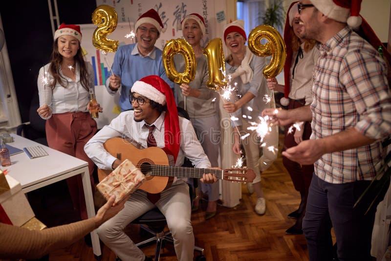 Personnes multi-ethniques heureuses de groupe d'affaires dans le chapeau de Santa à la partie de Noël photographie stock