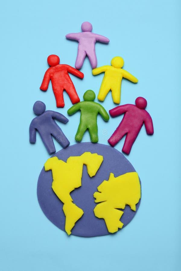 Personnes multicolores de bande dessin?e de p?te ? modeler sur le globe L'?puisement d'utiliser-et de la terre de plan?te, de la  photographie stock libre de droits