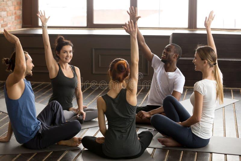 Personnes multiraciales enthousiastes soulevant des mains ensemble au yoga de groupe photographie stock