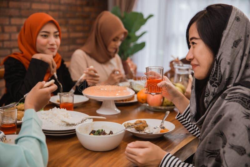 Personnes musulmanes ayant la coupure de dîner jeûnant ensemble photos stock