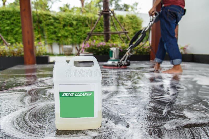 Personnes nettoyant le plancher noir de granit avec la machine et chimique thaïlandais images stock