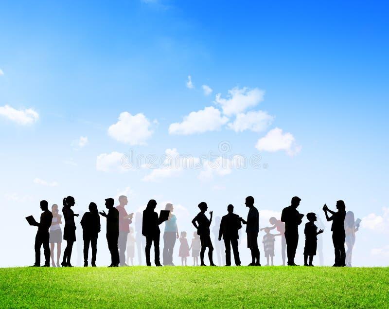 Personnes occasionnelles avec la mise en réseau sociale de familles dehors photos libres de droits