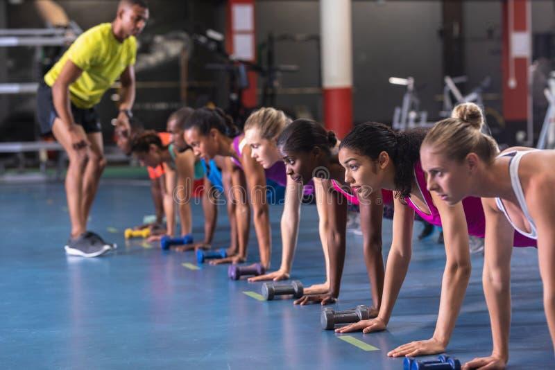 Personnes s'exerçantes d'entraîneur masculin pour exécuter l'exercice au centre de fitness photo stock