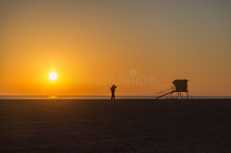 Personnes seules appréciant un coucher du soleil gentil dans le Huntington Beach, la Californie, Etats-Unis images libres de droits