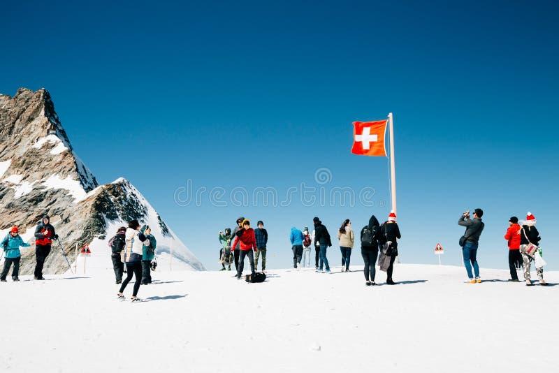 Personnes suisses de drapeau et de touriste sur le sommet neigeux de montagne de Jungfrau image stock
