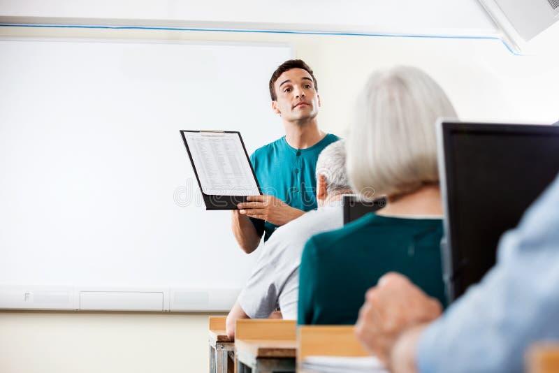 Personnes supérieures de Giving Lessons To de professeur dans le laboratoire de calcul image libre de droits