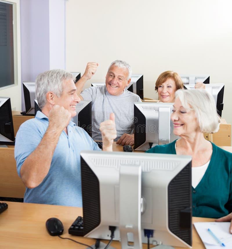 Personnes supérieures encourageant dans la classe d'ordinateur photographie stock libre de droits