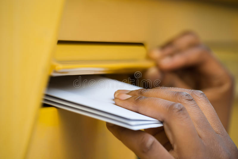 Persons hand som sätter in bokstaven i brevlåda royaltyfri bild