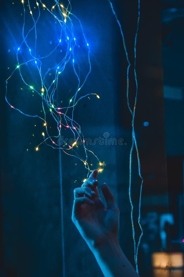 Persons hand som ut sträcker och når till färgrika fantasiljus på en tråd fotografering för bildbyråer
