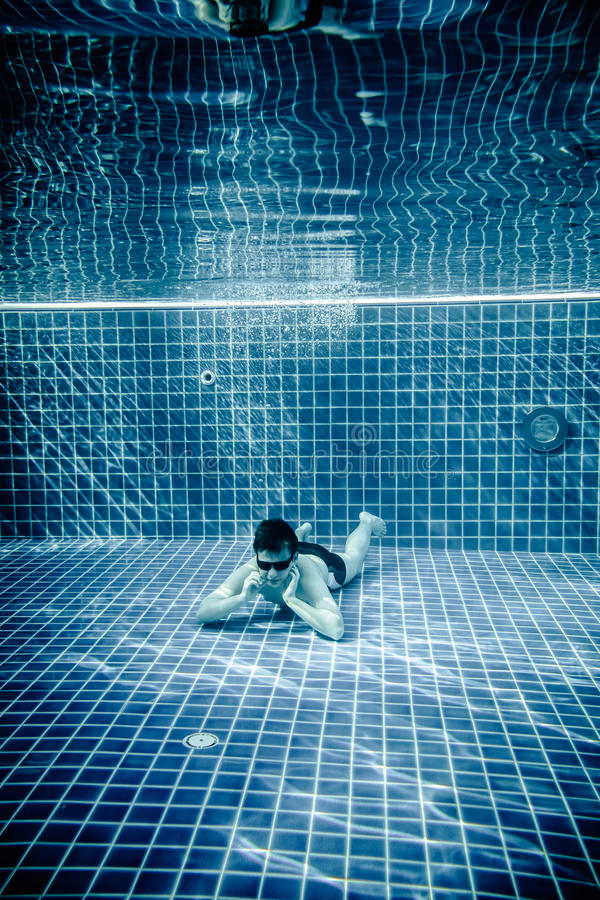 Persons lies under water in a swimming pool royalty free stock images