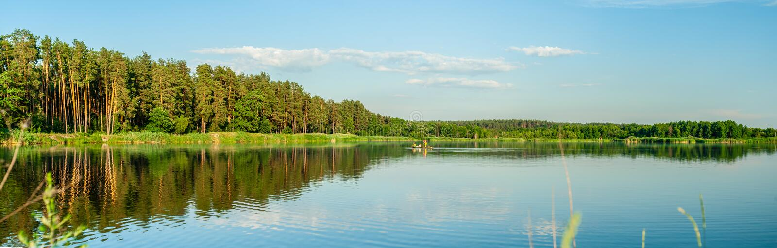 3 persons on the lonely boat in the middle of the lake that reflects forrest, under blue sky with clouds, panoramic background. Three persons on the lonely boat royalty free stock photo