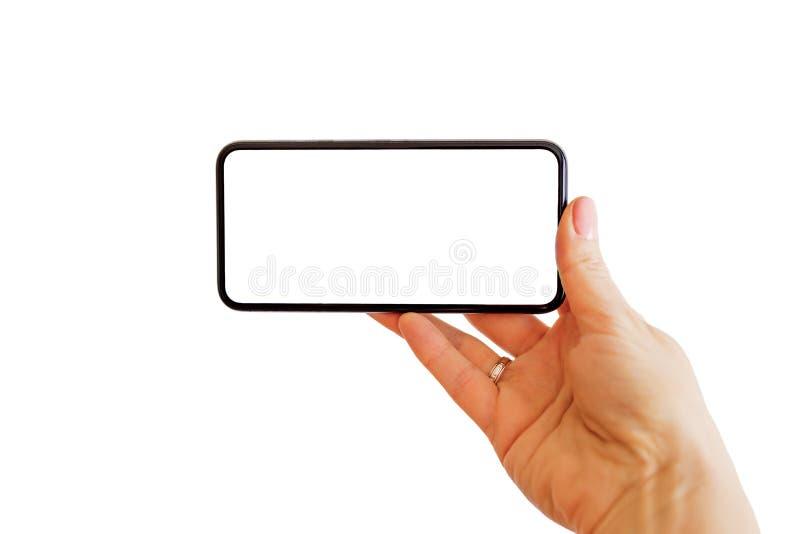 Personvisning något på telefonen med den tomma vita skärmen Mobil app-modell royaltyfria bilder