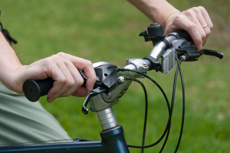 Persoon berijdende de fietss sturen van de fietsholding stock afbeeldingen