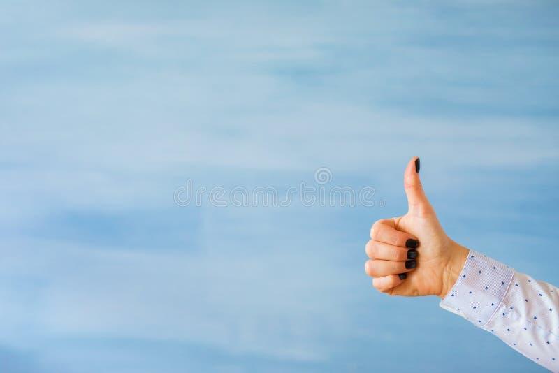 Persoon die duimen op handgebaar tonen op lege blauwe achtergrond stock fotografie
