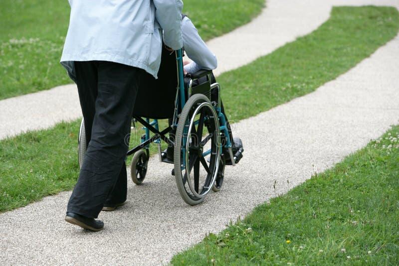 Persoon die een gehandicapte persoon duwt stock fotografie