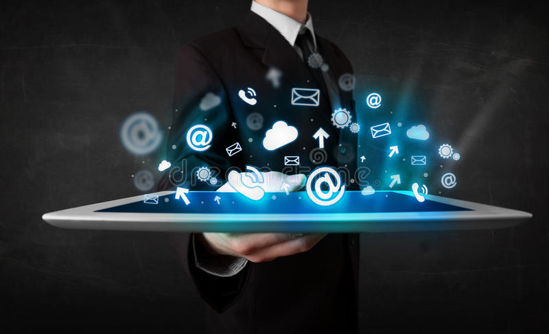 Persoon die een tablet met blauwe technologiepictogrammen en symbolen houden stock foto
