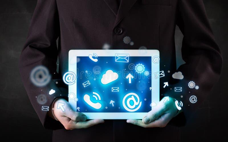 Persoon die een tablet met blauwe technologiepictogrammen en symbolen houden stock afbeeldingen