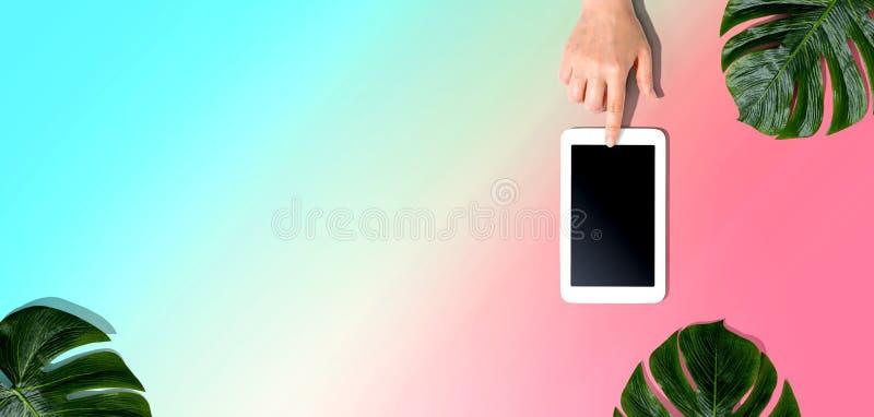 Persoon die een tabletcomputer met tropische bladeren gebruikt royalty-vrije stock afbeelding