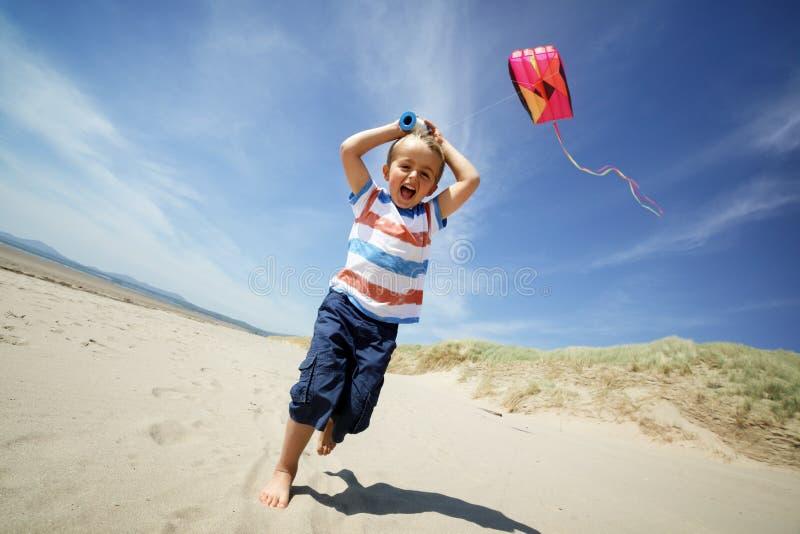 Persoon die een vlieger op een zonnige dag met jongen op het letten vliegt stock afbeeldingen