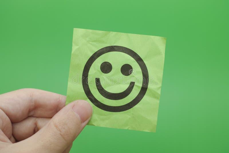 Persoon die Groenboeknota met Gelukkig Gezicht houden royalty-vrije stock fotografie