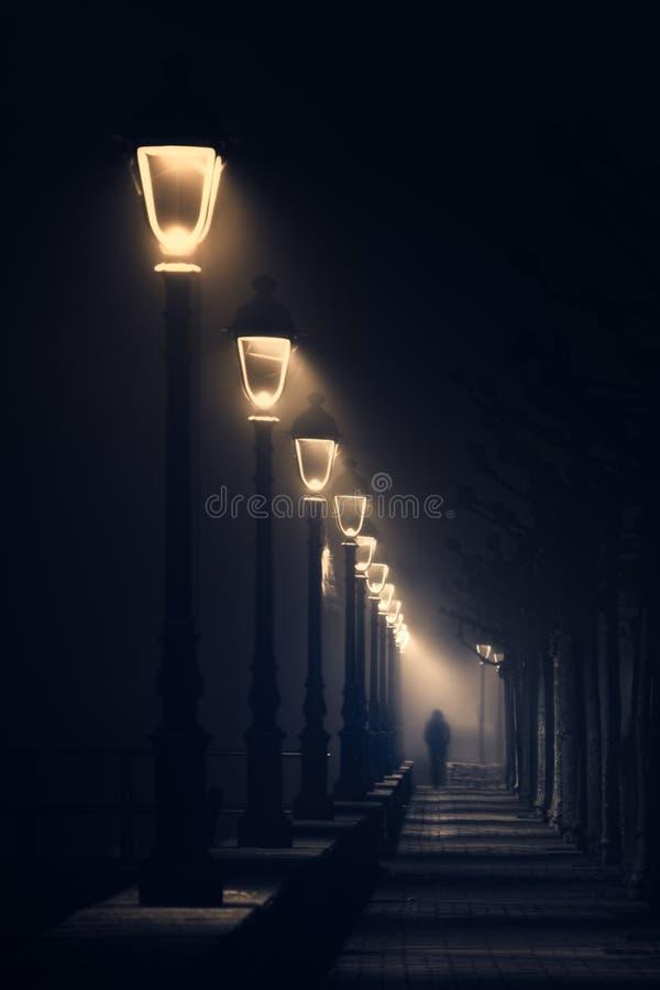 Persoon die op donkere die straat lopen met straatlantaarns wordt verlicht royalty-vrije stock foto's