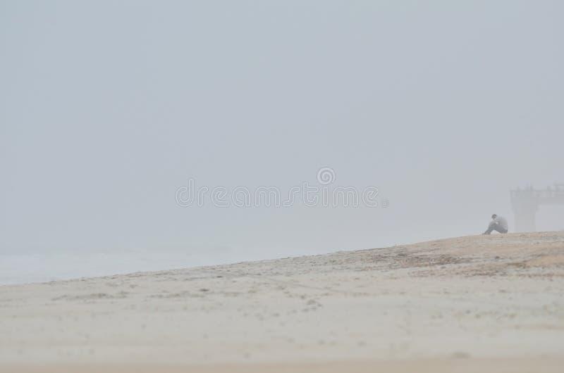Persoon die op nevelig strand wordt gezeten royalty-vrije stock foto