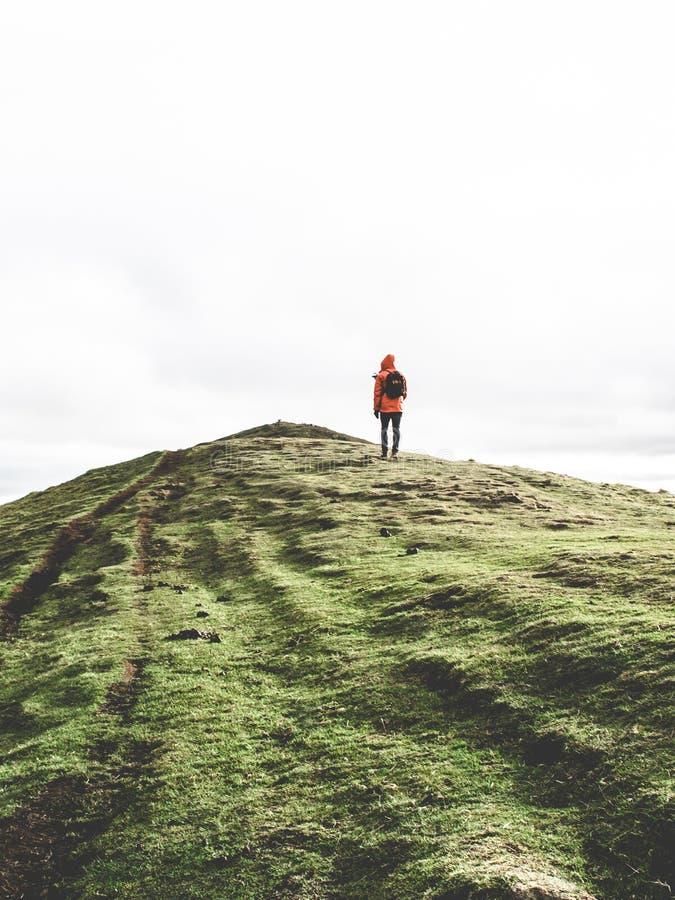 Persoon die oranje hoodie op groen gebergte in het witte luchtruim heeft royalty-vrije stock afbeeldingen