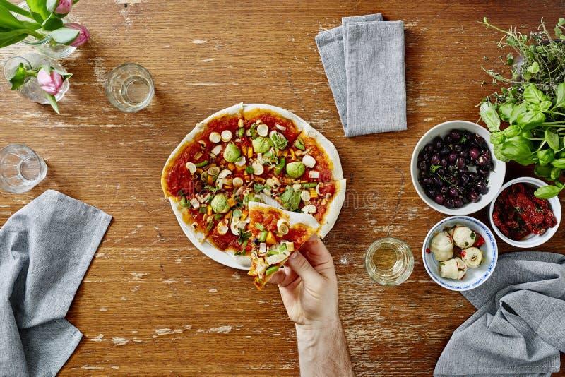 Persoon die plak van pizzastandpunt eten royalty-vrije stock foto