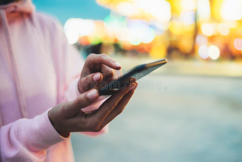 Persoon die vinger op het schermsmartphone richten op defocus achtergrond bokeh licht in avondstraat, hipster meisje die in hande stock fotografie