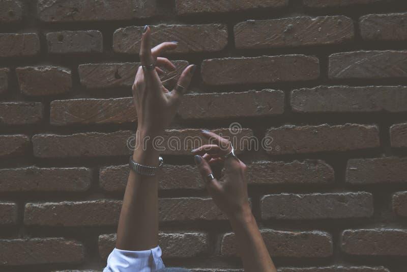 Persoon steekt zijn twee handen naast de bruine brick-muur royalty-vrije stock afbeeldingen