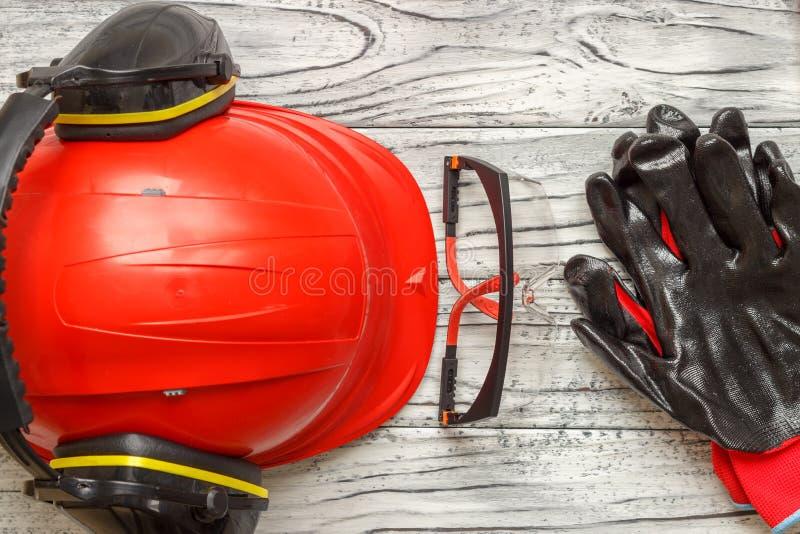 Persoonlijk beschermingsmiddel: de zwarte glazen van handschoenenbeschermende brillen op een houten achtergrond royalty-vrije stock afbeelding