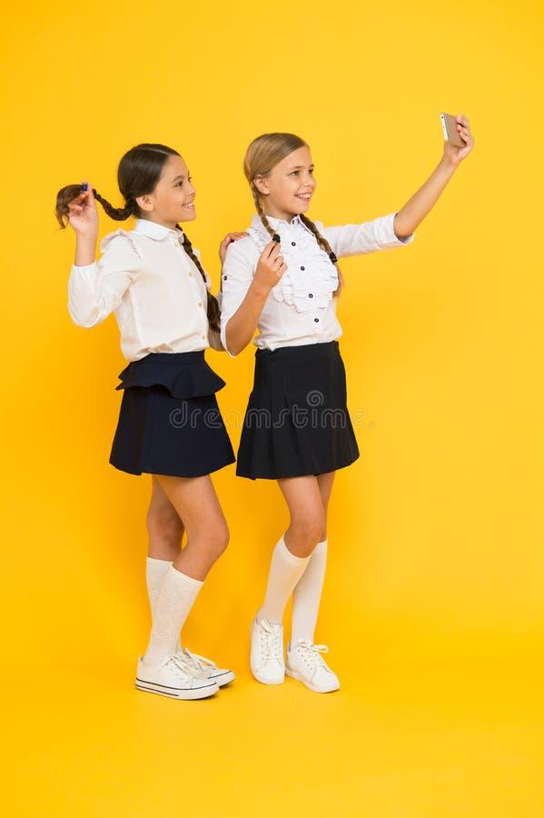 Persoonlijke blog Eenvormige meisjes de school neemt selfie smartphone Neem perfecte foto De meisjes willen enkel pret hebben sch stock foto