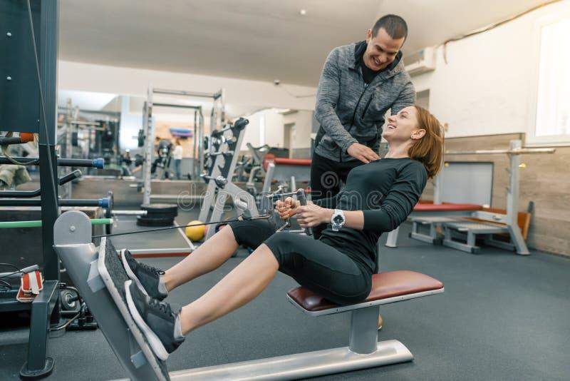 Persoonlijke geschiktheidsinstructeur die jonge vrouw in gymnastiek opleiden Sport, atleet, opleidend, gezond levensstijl en mens stock afbeeldingen