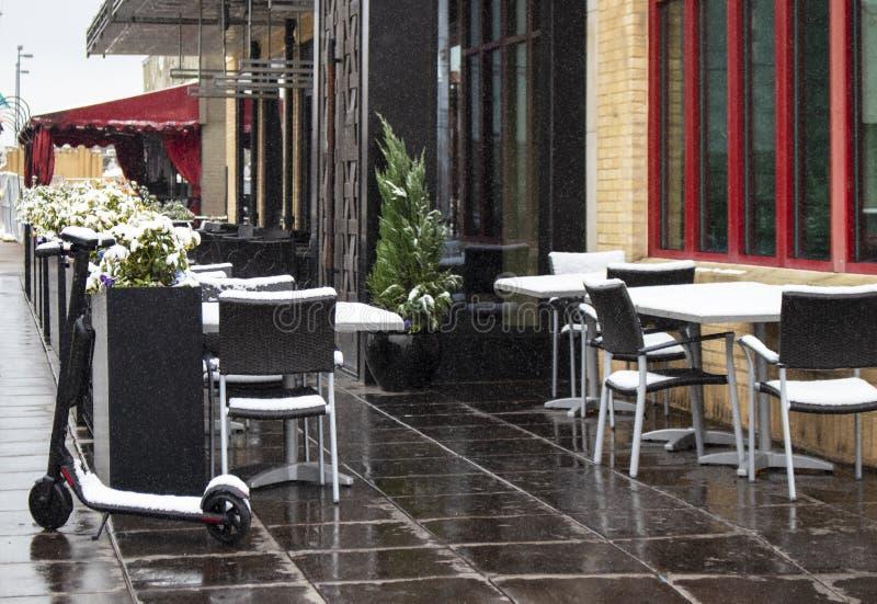 Persoonlijke mobilty elektrische die autoped door verlaten stoepkoffie wordt geparkeerd op sneeuwdag - rode & zwarte versiering stock afbeeldingen