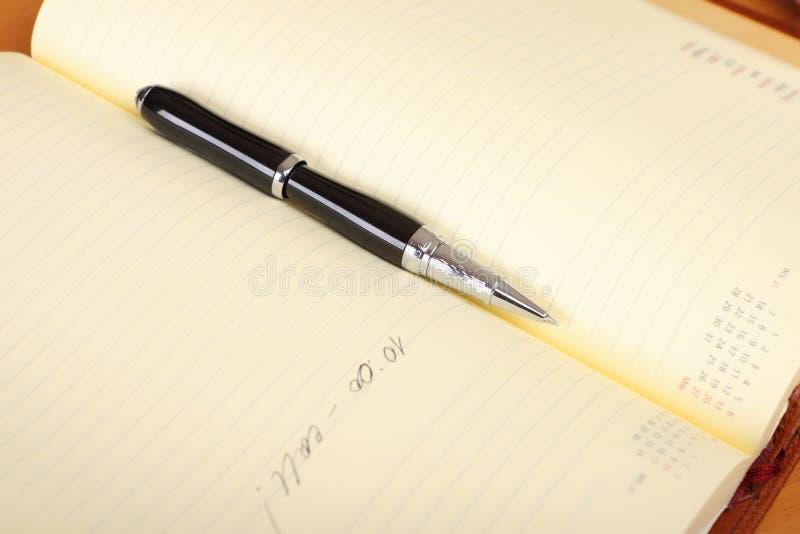 Persoonlijke organisator en pen op de lijst stock foto's