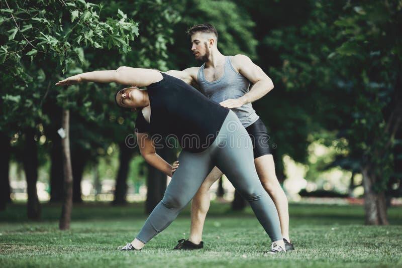 Persoonlijke trainer correcte cliënt die oefening doen stock afbeelding