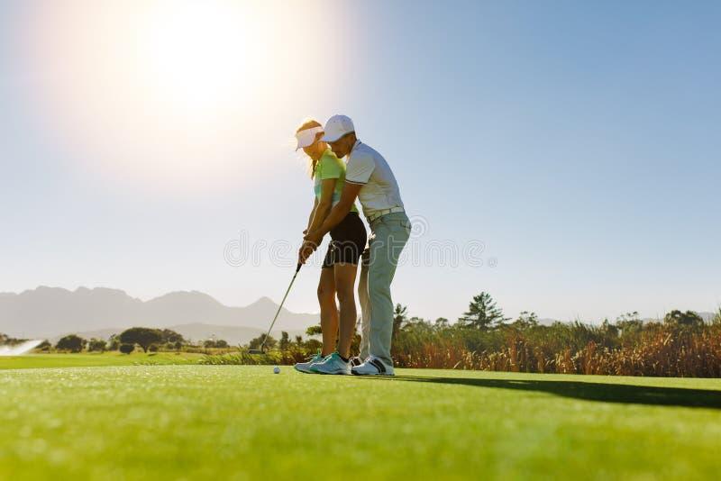 Persoonlijke trainer die les op golfcursus geven stock foto's