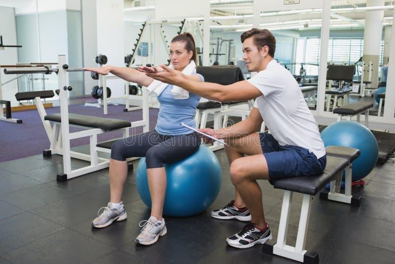 Persoonlijke trainer die met cliënt aan oefeningsbal werken stock afbeeldingen