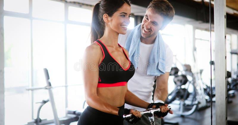 Persoonlijke trainer die met zijn cliënt werkt in de gymzaal royalty-vrije stock fotografie