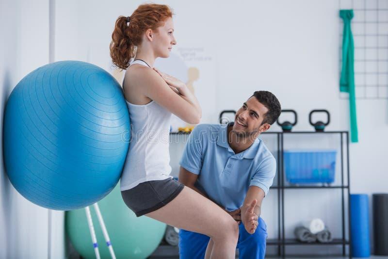 Persoonlijke trainer die sportvrouw helpen die met bal uitoefenen stock foto