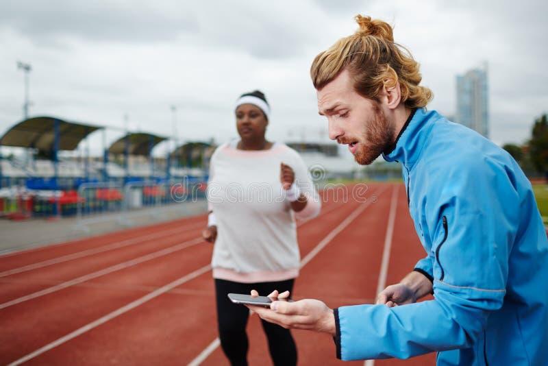 Persoonlijke trainer die tijd op smartphone meten stock afbeelding