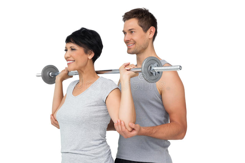 Persoonlijke trainer die vrouw met gewichtheffenbar helpen royalty-vrije stock foto