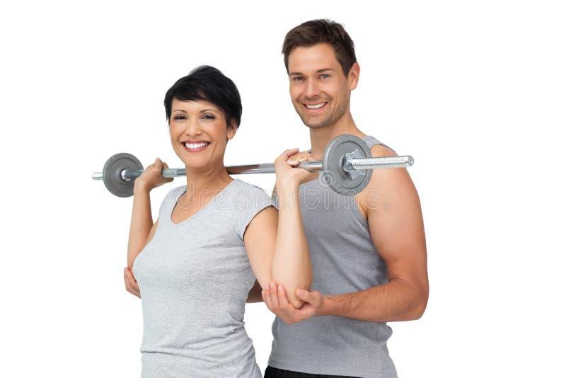 Persoonlijke trainer die vrouw met gewichtheffenbar helpen stock foto's
