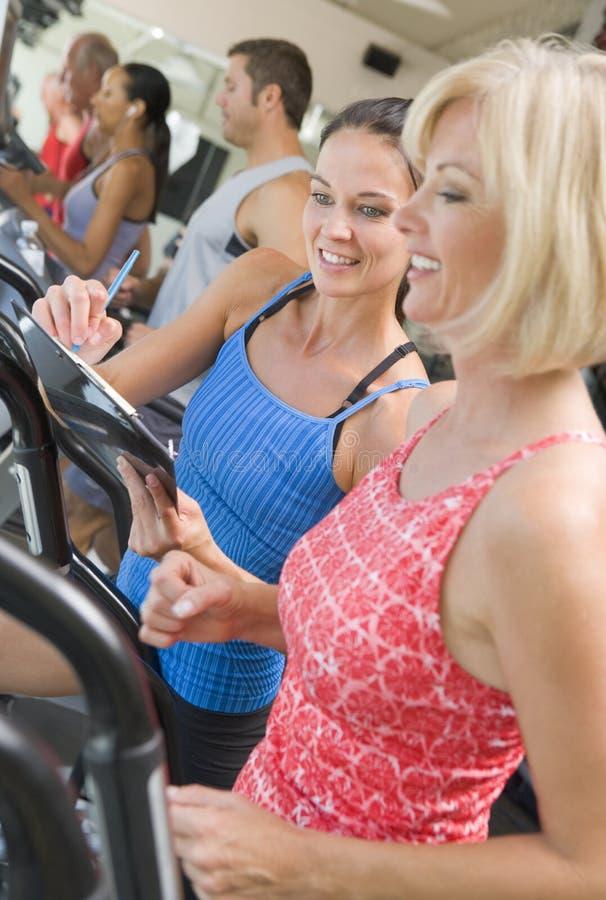 Persoonlijke Trainer die Vrouw op Tredmolen instrueert