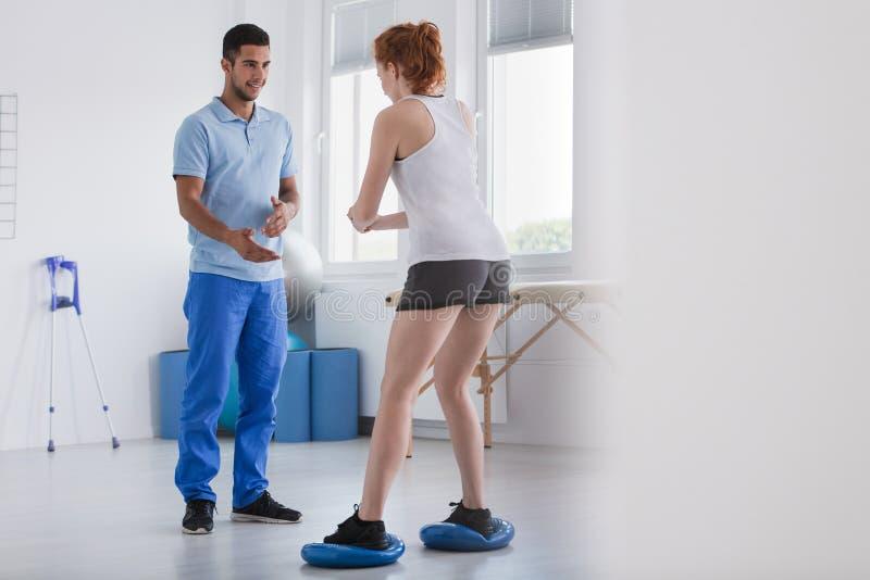Persoonlijke trainer met een vrouwelijke klant die hurkzit doen tijdens een training stock afbeelding