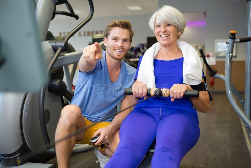 Persoonlijke trainer met hogere vrouw die het roeien machine met behulp van stock fotografie